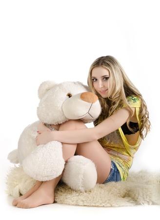 Sexy girl huggin a white toy teddy bear. photo