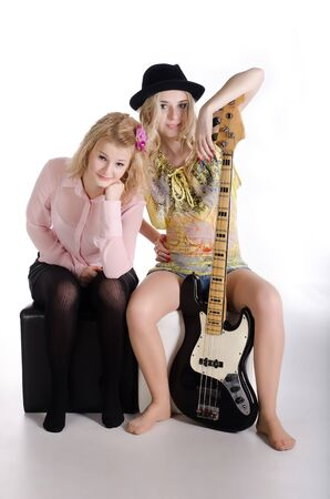 Two girls and guitar on white. photo