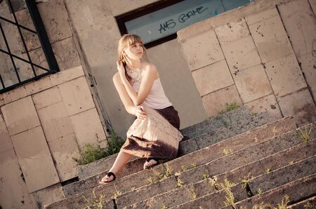 kharkov: Portrait of a pretty girl on an old stone stairway of an opera theatre on the sunset Stock Photo