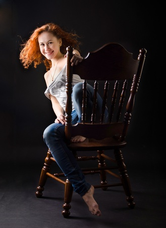 Red-haired beauty on an antique chair photo