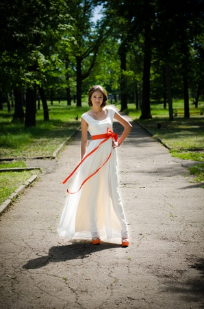 Girl in white dress with red ribbon in springtime forest in the middle of the park road  photo