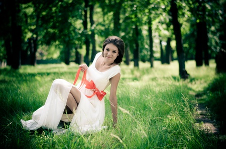 Girl in white dress with red ribbon in springtime forest  Stock Photo