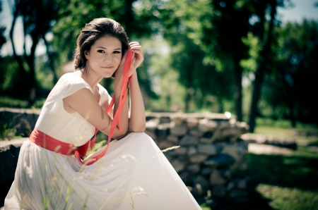 Girl in white dress with red ribbon in springtime forest  photo
