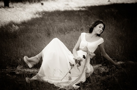 Girl in white dress with red ribbon in springtime forest  Black and white photo