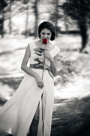 Black and white portrait of a girl with a vivid red rose in her hands  photo
