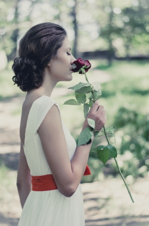 Cold toned portrait of a girl with a vivid red rose in her hands photo