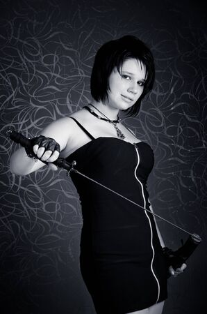 Girl in a black dress with a katana on grey background Stock Photo