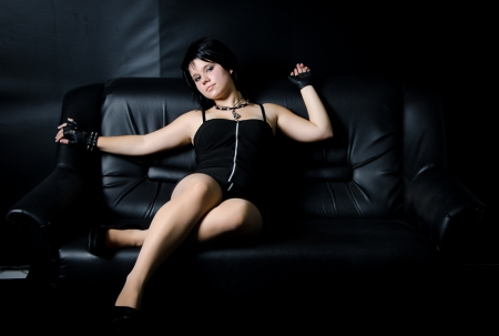 Beautiful raven haired girl on a black sofa