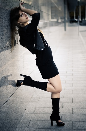 uppers: Girl in dark clother and gaiters by the marble wall
