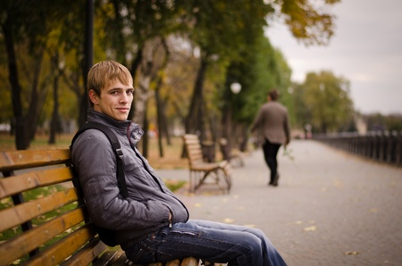 Man on a bench in a park by the river.