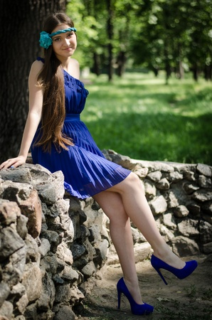 Prom girl in blue dress on rock fence photo