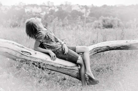 Black and white shot of a girl on a log. Stock Photo