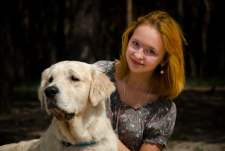 Girl with a big white dog in the forest.