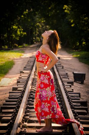 forest railroad: Beautiful girl standing on the railroad in the middle of the forest Stock Photo
