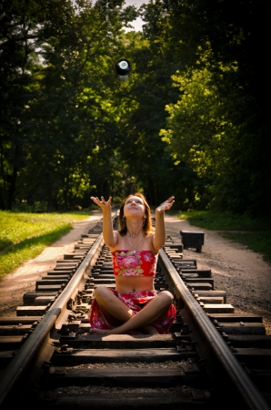 Beautiful girl throwing 8ball on the railroad in the middle of the forest Stock Photo