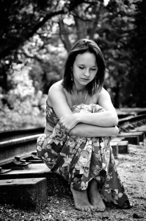 Sad girl on railway in black and white