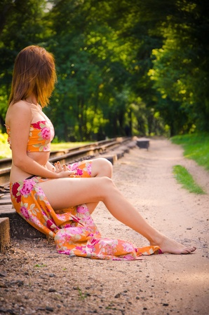 Beautiful girl on the railroad in the middle of the forest