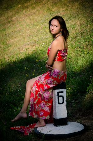 Beautiful girl sitting on the railroad sign in the middle of the forest Stock Photo