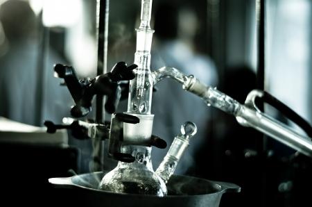 distillation: Qu�mica frasco con una reacci�n experimentando en ba�o de agua caliente y un vidrio qu�mico m�s fresco