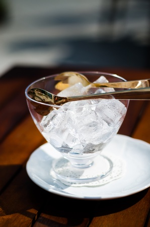 Ice cubes in a glass cup on a wooden table