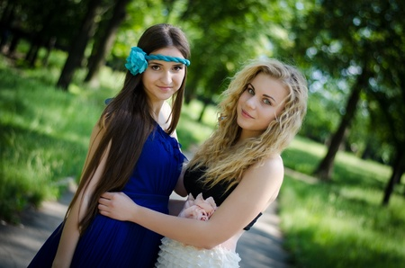 alike: Beautiful young girls in a park after the prom, smiling  Embracing each other