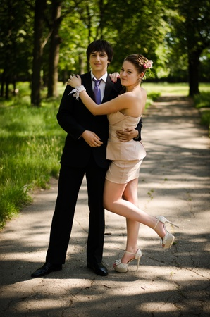 grass skirt: Young couple of high school seniors after the prom in a summer park  Stock Photo