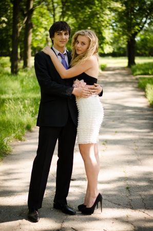 Young couple of high school seniors after the prom in a summer park. photo