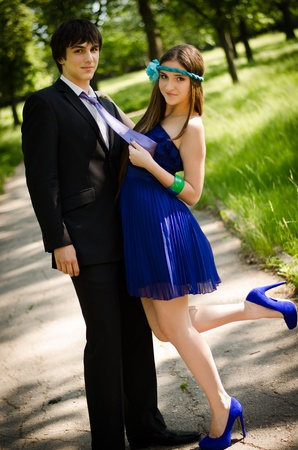 Young couple of high school seniors after the prom in a summer park. Beautiful brunette in blue dress and shoes pulling mans tie.