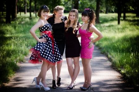 tacones negros: Cuatro chicas jovenes hermosas en un parque después de la fiesta de graduación. Riendo y sonriendo. Foto de archivo