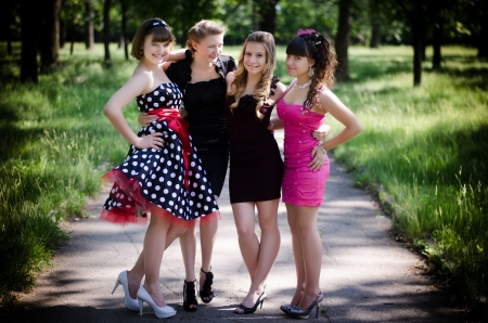 Four beautiful young girls in a park after the prom. Laughing and smiling.