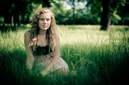 Portrait of young curly blonde in summer park sitting in high wild grass photo