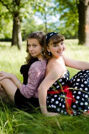 Girls sitting in grass back-to-back smiling in a summer park. Stock Photo