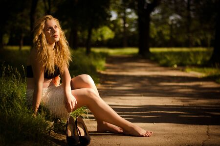 Young beautiful blonde girl sitting bare-foot at the edge of road with her shoes near her. Warm sunset light. photo