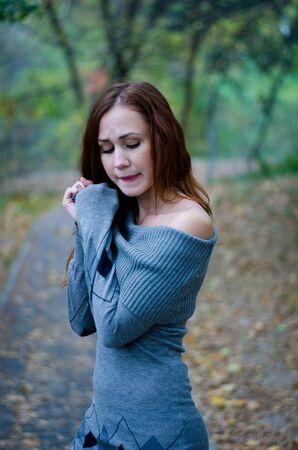Sad girl alone in a dark forest Stock Photo
