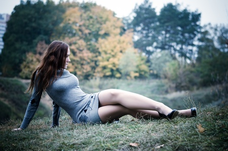 Beautiful girl in an autumn park looking away photo