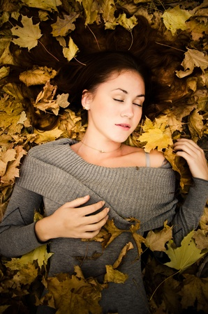Beautiful girl lying in the bed of autumn leaves