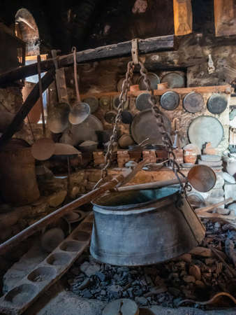 Ancient utensils and hearth with a boiler in the ancient kitchen in the Megala Meteora monastery in Meteora region, Greece