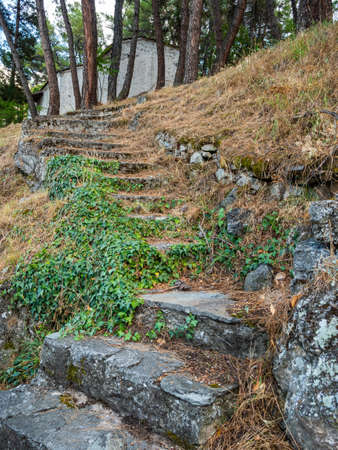 Ancient stone steps up the slope to the building of a chapel in Greece