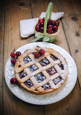 dieta: Italian cherry crostata cake on wooden table