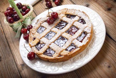 Italian cherry crostata cake on wooden table