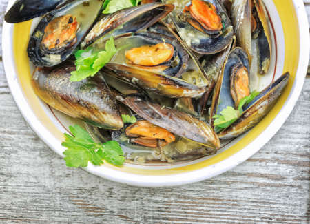 mussel: Mussel soup with fresh parsley on wooden table Stock Photo
