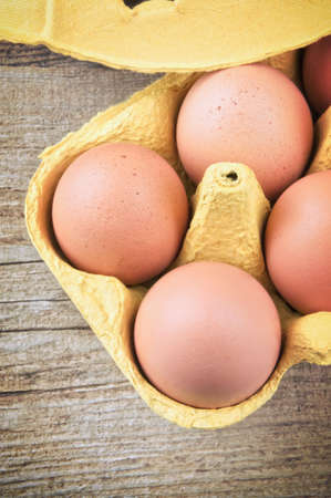 Eggs in storage box on wooden table