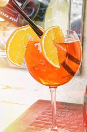 Spritz aperitive in a wine glass with slices of orange