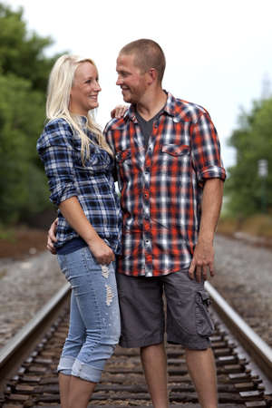 flannel: Happy young attractive couple on railroad tracks
