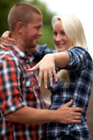 Happy young attractive couple showing off engagement ring Reklamní fotografie