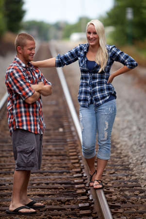 Happy young attractive couple on railroad tracks