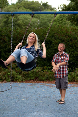 Happy young attractive couple playing on swings Reklamní fotografie