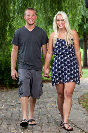 Happy young attractive couple holding hands Reklamní fotografie