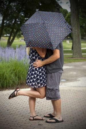 Happy young attractive couple behind umbrella