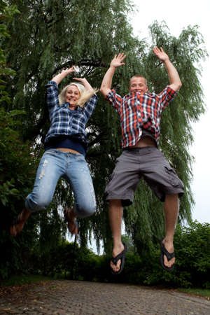 Happy young attractive newlyweds jumping